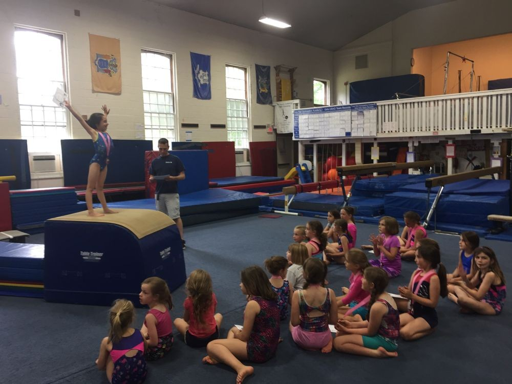 Recreational Gymnasts receiving a medal and certificate of completion at Iron Rail's annual Rec Exhibition